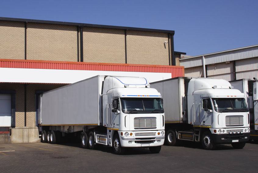 A pair of refrigerated transporters at a food warehouse loading